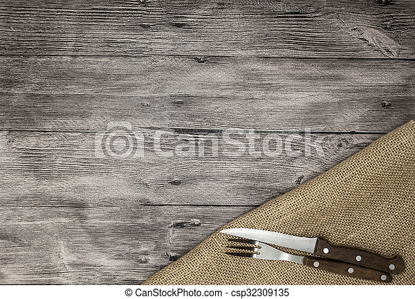 Beautiful wooden background with napkin knife and fork. Fine background for the menu of restaurants and cafes - csp32309135
