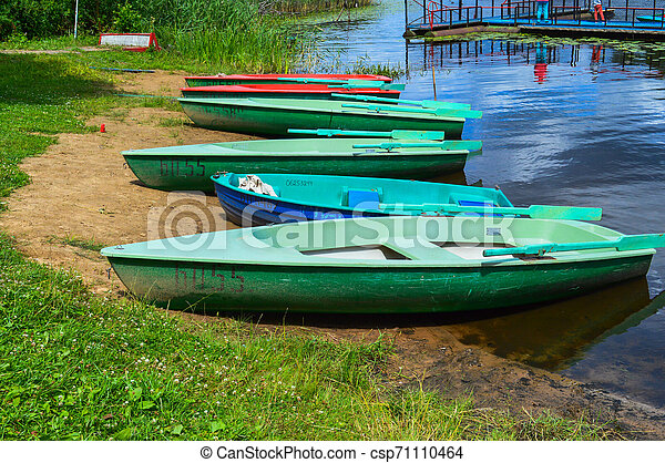 Beautiful wooden multicolored boats with oars on the beach for walks along the river, lake, sea, ocean in a nature park on the shore - csp71110464