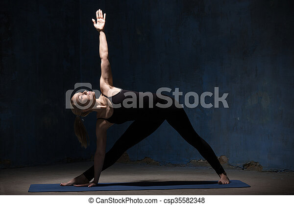 beautiful yoga woman doing extended triangle pose