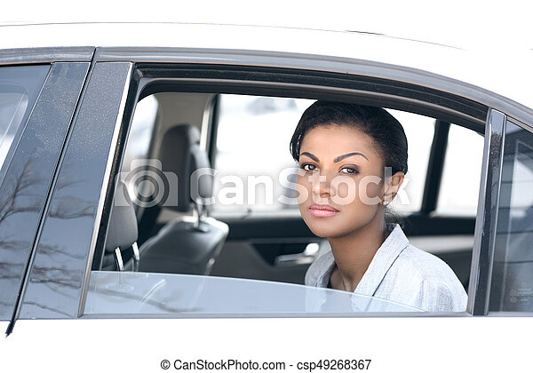Beautiful young african american woman sitting in car and looking at camera - csp49268367