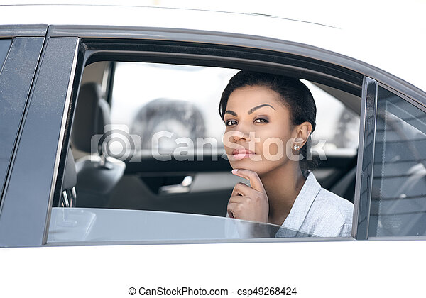 Beautiful young african american woman sitting in car and looking at camera - csp49268424