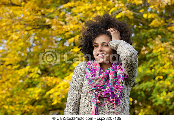 Beautiful young african american woman smiling with hand in hair - csp23207109