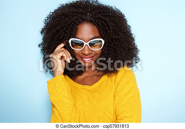 beautiful young african woman in stylish sunglasses on blue background - csp57931813