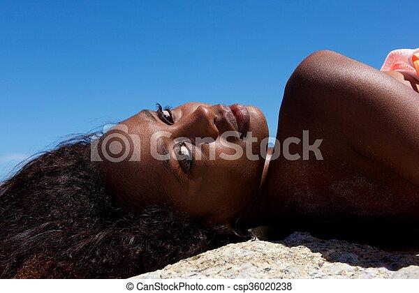 Beautiful young african woman lying outdoors - csp36020238