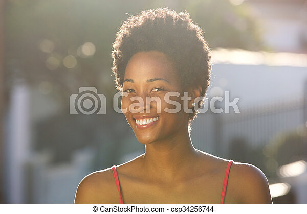 Beautiful young african woman smiling outdoors - csp34256744