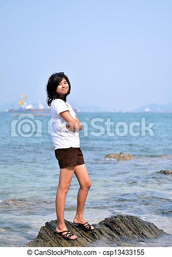 Beautiful young asian woman on beach - csp13433155