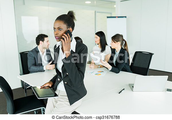 Beautiful, young, black businesswoman holding a tablet at an office meeting and getting bad news on the phone - csp31676788