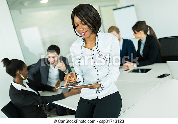 Beautiful, young, black businesswoman looking at a tablet at an office meeting - csp31713123
