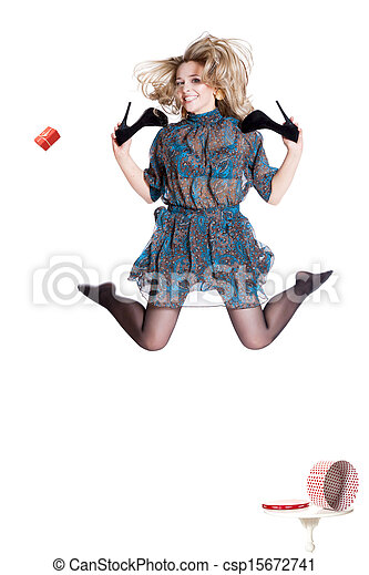 Beautiful young blonde jumping with shoes in hand - csp15672741