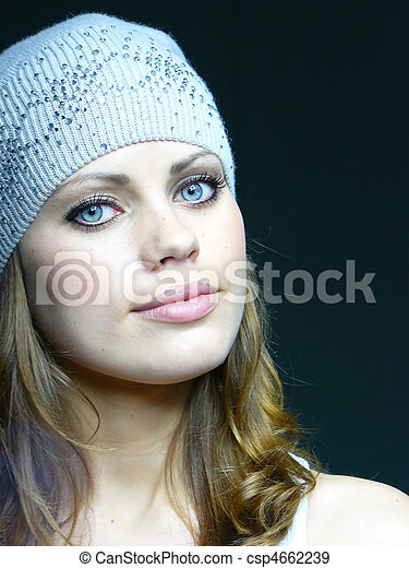 beautiful young blue-eyed girl in a grey cap with pastes - csp4662239
