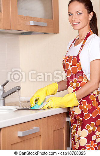 Beautiful young brunette washing dishes. attractive girl standing in apron and using detergents - csp18768025