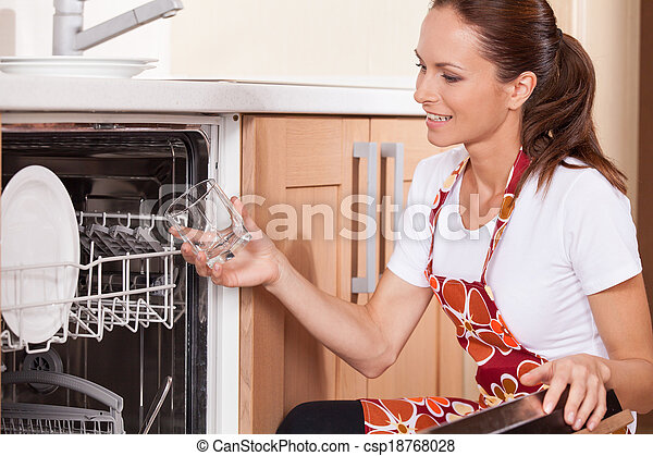 Beautiful young brunette washing dishes. attractive housewife taking dishes from dishwasher - csp18768028