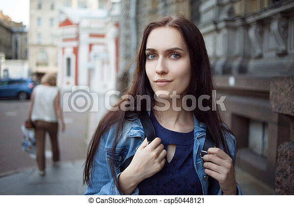 Beautiful young brunette with a backpack in the city - csp50448121
