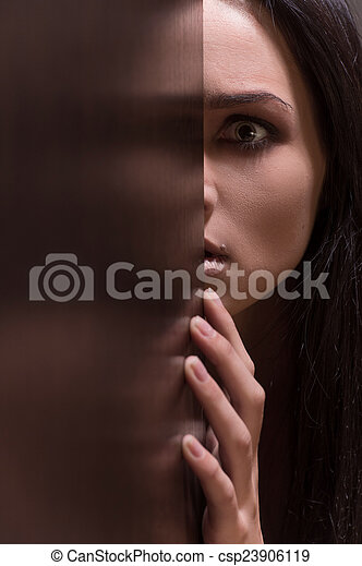 Beautiful young brunette woman looking scared. fear on female face with half face in doorway - csp23906119