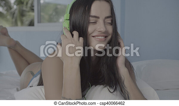 Beautiful young brunette woman lying on bed using her smartphone and headphones - csp40066462