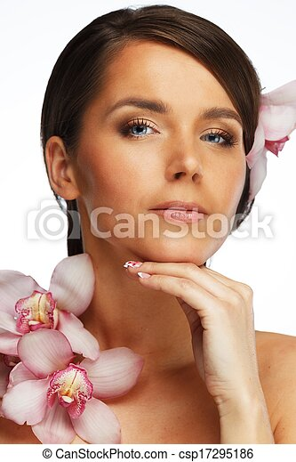 Beautiful  young brunette woman with orchid flowers - csp17295186
