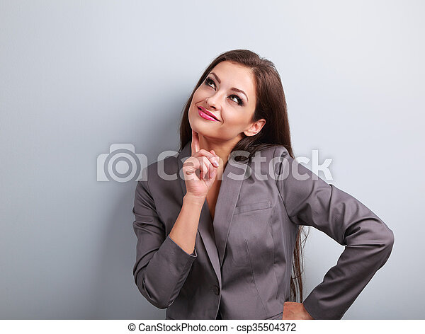 Beautiful young business woman in suit thinking and looking up on blue background - csp35504372