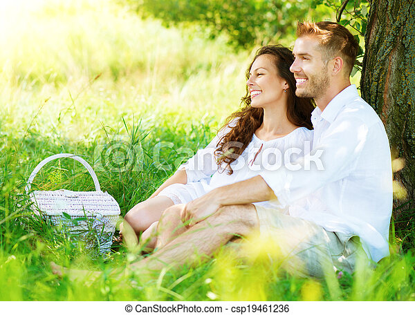 Beautiful Young Couple Having Picnic in Countryside - csp19461236