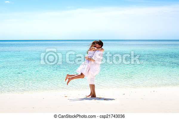 Beautiful young couple hugging on a stunning tropical beach - csp21743036