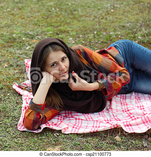 beautiful young girl hipster dreams of lying on a magic meadow in spring. Hipster beautiful girl with the camera in a field in spring - csp21100773