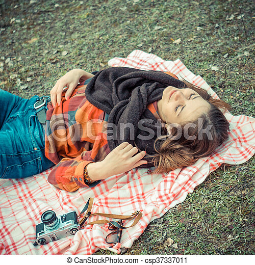 beautiful young girl hipster dreams of lying on a magic meadow in spring. Hipster beautiful girl with the camera in a field in spring - csp37337011