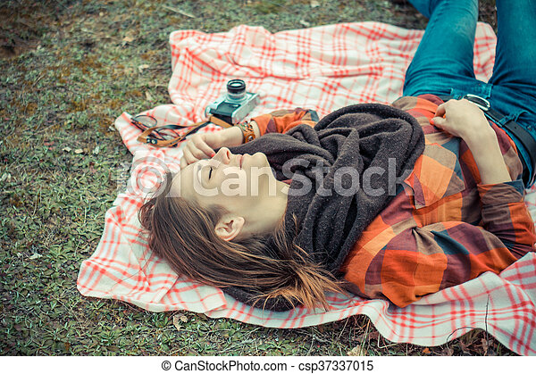 beautiful young girl hipster dreams of lying on a magic meadow in spring. Hipster beautiful girl with the camera in a field in spring - csp37337015