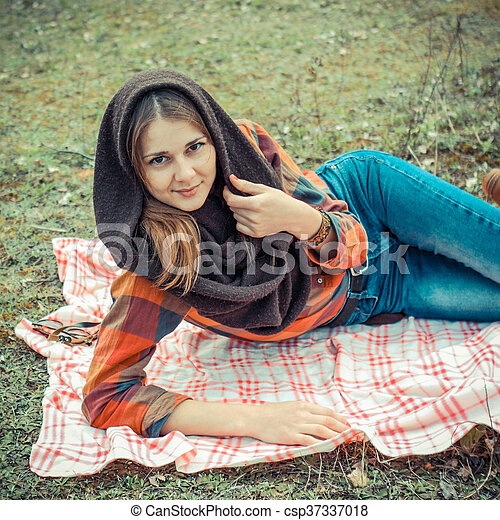 beautiful young girl hipster dreams of lying on a magic meadow in spring. Hipster beautiful girl with the camera in a field in spring - csp37337018