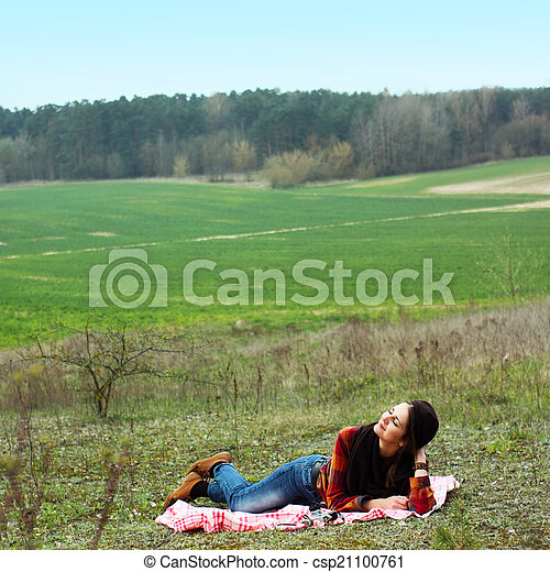 beautiful young girl hipster dreams of lying on a magic meadow in spring. Hipster beautiful girl with the camera in a field in spring - csp21100761