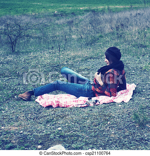 beautiful young girl hipster dreams of lying on a magic meadow in spring. Hipster beautiful girl with the camera in a field in spring - csp21100764