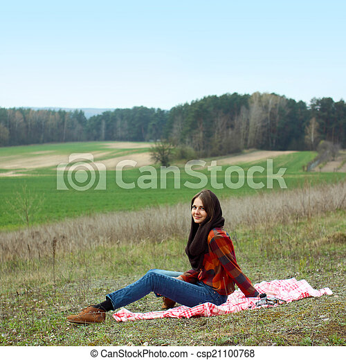 beautiful young girl hipster dreams of lying on a magic meadow in spring. Hipster beautiful girl with the camera in a field in spring - csp21100768