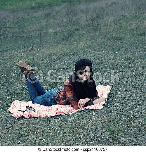 beautiful young girl hipster dreams of lying on a magic meadow in spring. Hipster beautiful girl with the camera in a field in spring - csp21100757