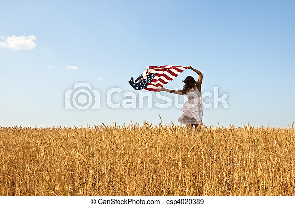 Beautiful young girl holding an American flag in the wind in a field of rye. Summer landscape against the blue sky. Horizontal orientation. - csp4020389