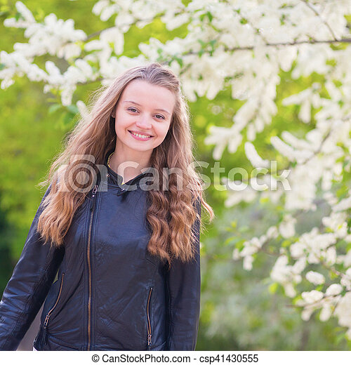 Beautiful young girl in a park on a spring day - csp41430555
