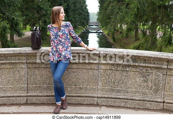 Beautiful young girl on the old stone bridge - csp14911899