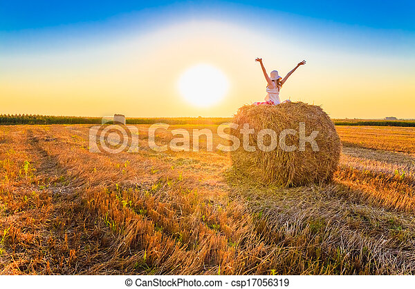 Beautiful young girl staying on haystack in sunny day - csp17056319