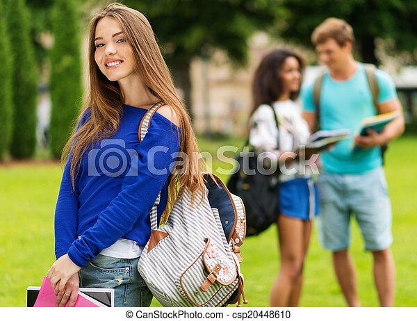 Beautiful young girl student in a city park on summer day  - csp20448610