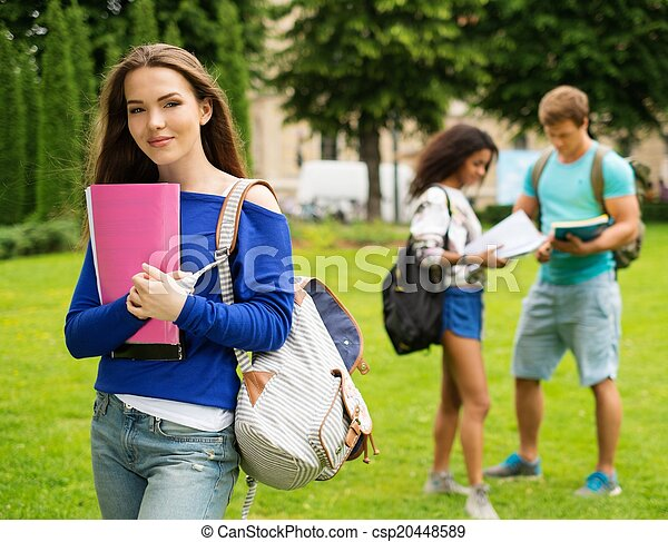 Beautiful young girl student in a city park on summer day  - csp20448589