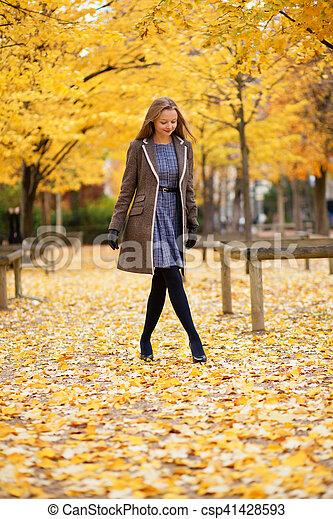 Beautiful young girl walking in park on a fall day - csp41428593
