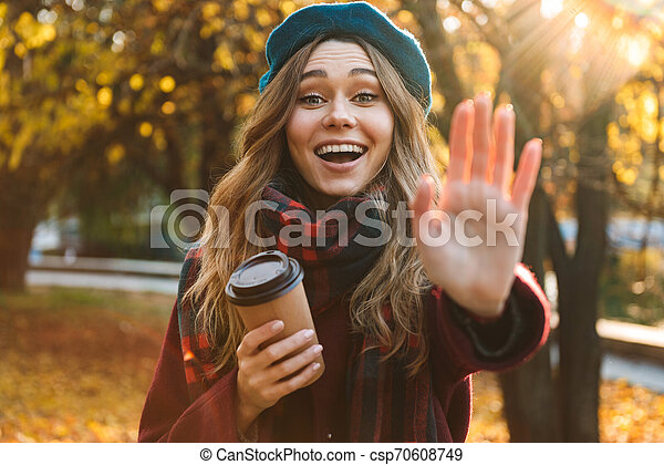 Beautiful young pretty woman walking outdoors in autumn spring park. - csp70608749