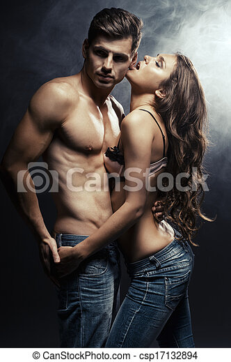 Beautiful young smiling couple in love embracing indoor - csp17132894