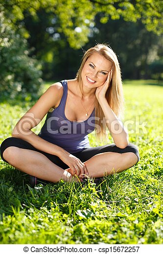 Beautiful young smiling sporty girl sitting on a grass in a park - csp15672257