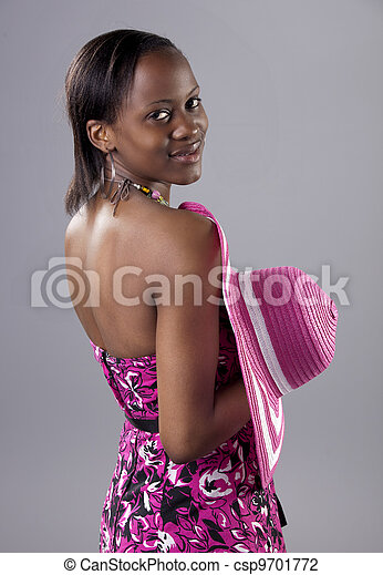 Beautiful young South African woman in bright colours looking back over her shoulder. - csp9701772