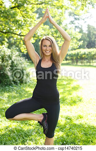 Beautiful young sporty girl doing fitness exercise in a park on sunny day - csp14740215