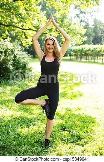 Beautiful young sporty girl doing fitness exercise in a park on sunny day - csp15049641