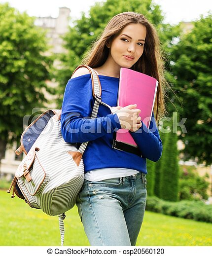 Beautiful young student girl in a city park on summer day - csp20560120