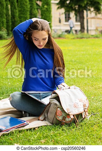 Beautiful young student girl in a city park on summer day - csp20560246