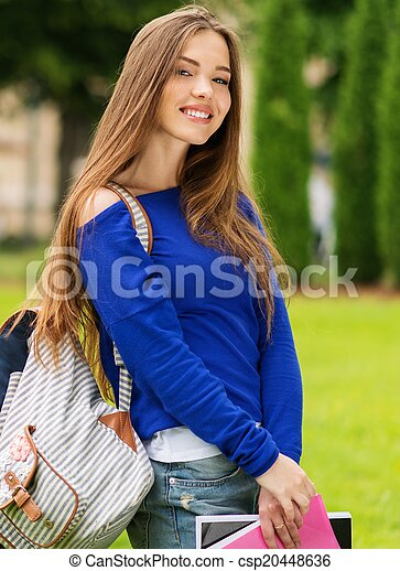 Beautiful young student girl in a city park on summer day - csp20448636