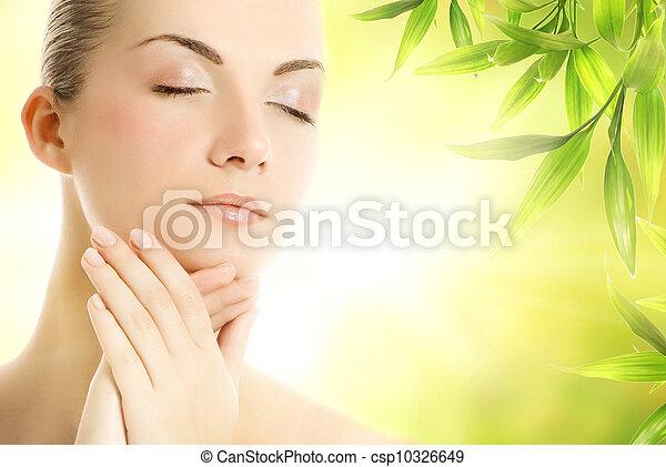 Beautiful young woman applying organic cosmetics to her skin - csp10326649