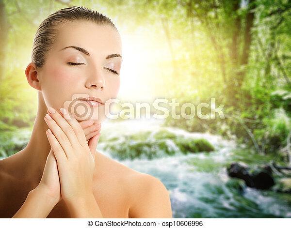Beautiful young woman applying organic cosmetics to her skin - csp10606996