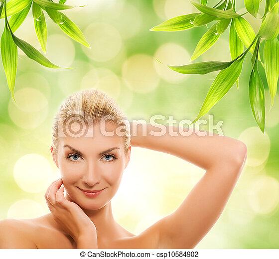 Beautiful young woman applying organic cosmetics to her skin - csp10584902